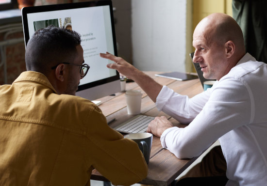 Two Human Resource people in discussion in front of a computer screen
